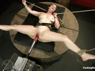 Fucking whore Bella Rossi is tied up with strings on table and gets fucked by a machine with a big dildo. Having also a vibrator on her clitoris, she