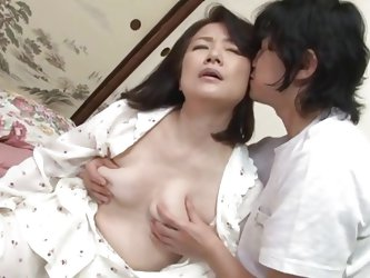 This old mature Japanese lady barely looks a day over 40 but she is actually 50! She has a young boy toy that comes over to please her. He unbuttons h