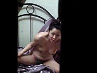 Spy cam voyeur video of Korean woman chilling out naked and smoking a cigarette on a hotel room bed. This was probably taken by a horny neighbor, sinc
