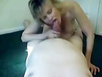 The blonde mature lady stands on the floor on all four. Her husband moves behind her and penetrates her cunt. He fucks her had in doggy style. In the