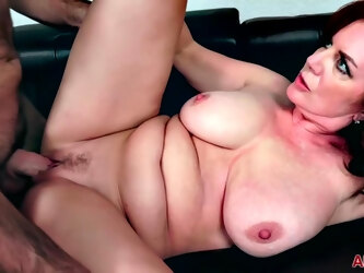Mature, red haired woman, Andi James is riding a rock hard dick, on the sofa