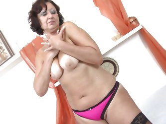 This sexy curly-haired mature lady is looking sexy wearing her pink lingerie. She strips down to reveal her floppy breasts that are so suckable. She p