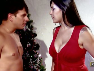 beautiful busty milf Raylene dressed in red bends over for hot guy and takes his dick in her fuck hole doggy style beside the Christmas tree.