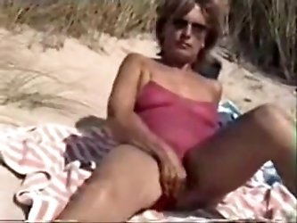 Mature with hairy love tunnel filmed naked in clip scene on the public beach.