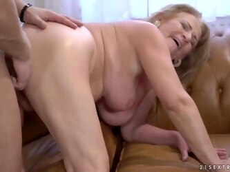 Mature blonde woman, Sally G and a younger guy are fucking in her huge apartment