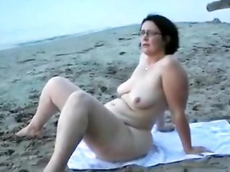 My four eyed brunette wife loves to expose her pussy on the nudist beach. She is big bottomed mature woman with small saggy tits.