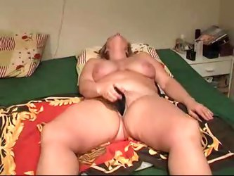 large white lady lies on her mattress bare naked and inserts long black vibrating dildo in her pussy. Her big tits bounce. All the while, her husband