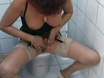The action takes place is a public restroom where a short hair mature woman with a small pair of tits starts rubbing herself in all kind of positions.