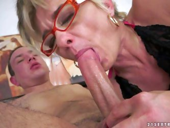Cock hungry mature short haired blonde whore with slim body and provocative glasses in black lingerie gives amazing blowjob to young horny buck and ri