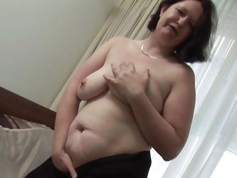 She takes off her clothes and massages her boobs while looking at the camera. Daisy knows that we are watching her and that makes this whore horny! No
