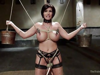 This big breasted slave is tied up in rope bondage, and the two masters want to use her as a fuck toy. They unhook her and one pounds her hard from be