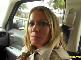 Attractive seductive young looking blonde milf with pretty face and beautiful eyes gets filmed in point of view while driving around with turned on di