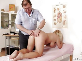 This blonde slut is completely naked at the doctor. The doctor starts examining her big breasts with large and sexy nipples. After that he takes her p
