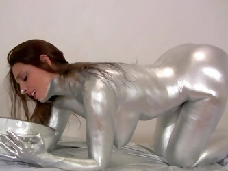 Nude beauty covers herself in silver paint of a kinky solo