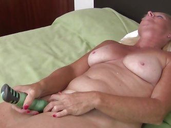 This dirty blonde mature has wrinkly, dry skin and a pair of natural tits. She lays back on her bed and sticks her vibrator in her old cunt. She moans